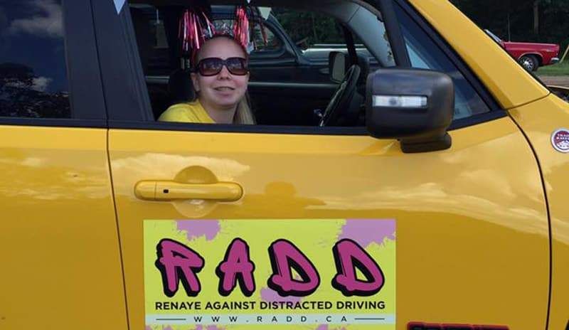 Renaye in a vehicle displaying the RADD logo.